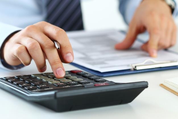 Vista ravvicinata delle mani del contabile o dell'ispettore finanziario che fanno rapporto, calcolo o controllo dell'equilibrio. finanze domestiche, investimenti, economia, risparmio di denaro o concetto di assicurazione Foto Premium