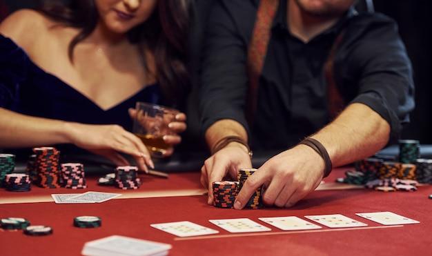 Chiuda sulla vista delle mani eleganti dei giovani che giocano a poker nel casinò Foto Premium