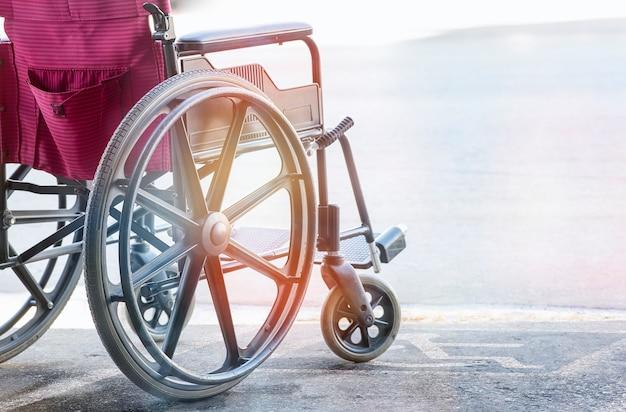 Chiuda sulla vista della sedia a rotelle vuota con simbolo di handicap pavement Foto Premium
