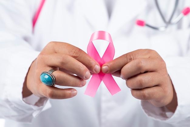 Chiuda sulla vista delle mani di medico femminile che tengono nastro rosa del cancro al seno. Foto Premium