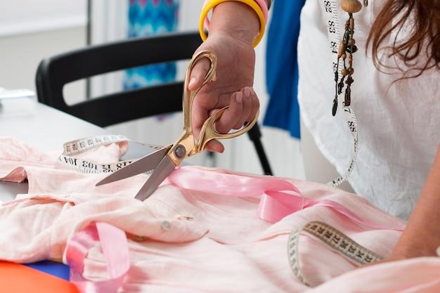 Vista ravvicinata delle mani femminili del creatore del vestito che tagliano qualcosa. la sarta lavora nel suo atelier. vestiti fatti a mano Foto Premium