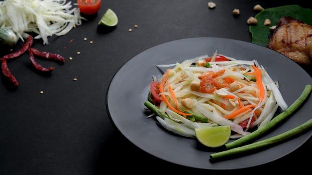 Chiuda sulla vista dell'insalata di papaia sulla banda nera, sulla griglia del pollo sul taro verde e sugli ingredienti Foto Premium