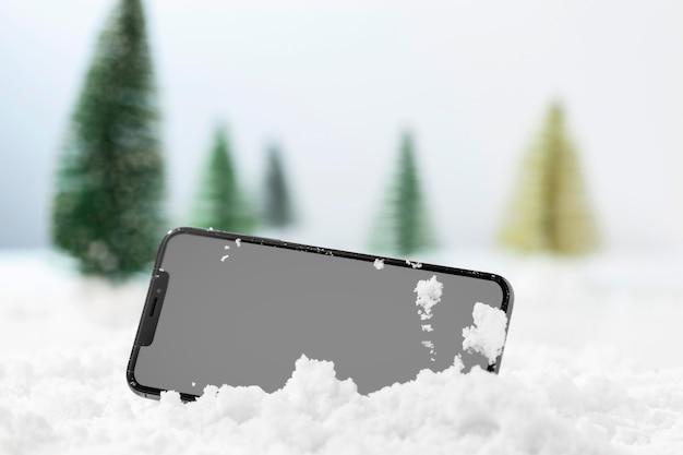 Vista ravvicinata di smartphone nella neve Foto Premium