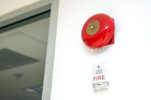 Campana antincendio rossa montata a parete ravvicinata e spia lampeggiante nei concetti di costruzione del sistema di prevenzione e sicurezza dell'allarme antincendio Foto Premium