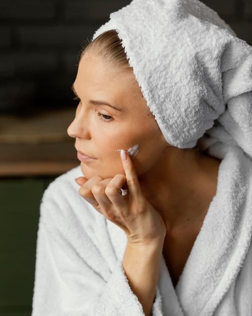 Chiuda sulla donna che applica crema per il viso Foto Premium