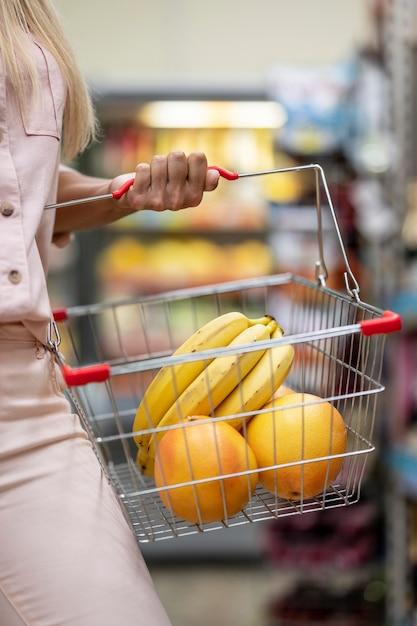 Carrello di trasporto della donna del primo piano con i frutti Foto Premium