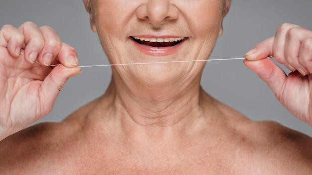 Filo interdentale della holding della donna del primo piano Foto Premium