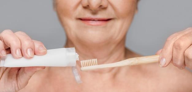 Donna del primo piano che tiene spazzolino da denti e dentifricio Foto Premium