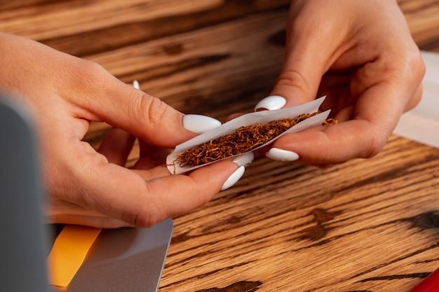 Chiuda in su della donna che fa sigaretta arrotolata a mano al tavolo di legno Foto Premium