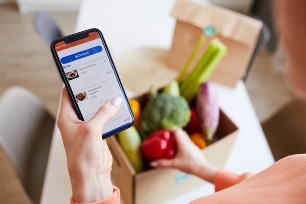 Primo piano della donna che ordina cibo online dal suo telefono cellulare a casa Foto Premium