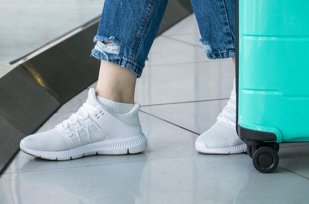 Primo piano delle scarpe bianche della donna in aeroporto Foto Premium