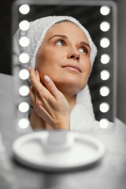Chiuda sulla donna che tocca il suo fronte Foto Premium