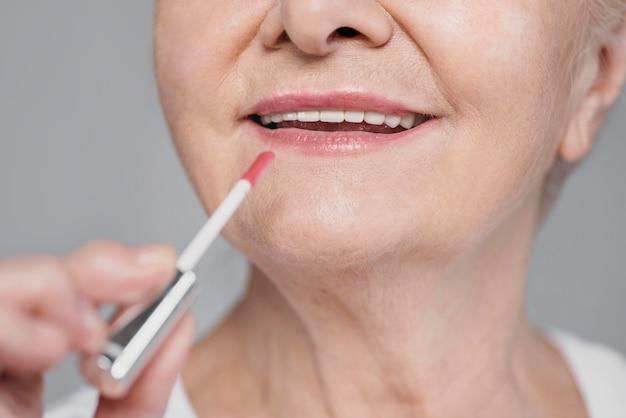 Donna del primo piano utilizzando lucidalabbra Foto Premium