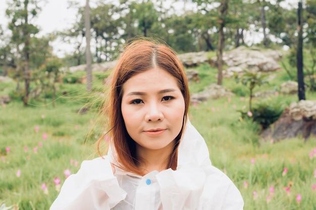 Close up donna indossare impermeabile stand nella foresta pluviale Foto Premium
