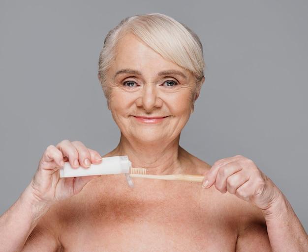 Donna del primo piano con spazzolino da denti e dentifricio Foto Premium