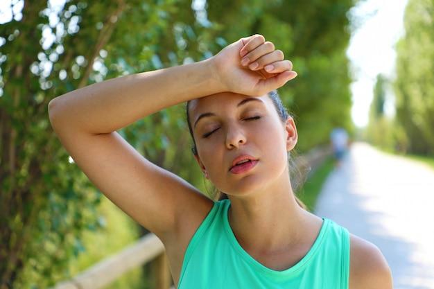 Chiuda in su della giovane donna che prende una pausa dall'allenamento fuori stanco con il braccio sopra la testa. Foto Premium