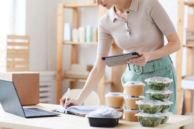Primo piano di giovane donna utilizzando la tavoletta digitale e prendere appunti nel blocco note lei lavora nel servizio di consegna di cibo Foto Premium