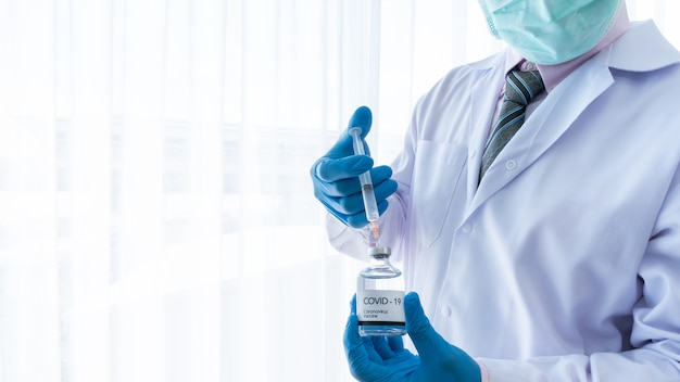Primo piano uomo asiatico medico indossare la maschera e riempire la siringa in bottiglia di vetro del vaccino virus covid-19 o corona Foto Premium