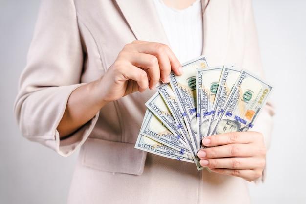 Primo piano delle mani della donna di affari che contano le banconote in dollari americani dei soldi su bianco. concetto di denaro. Foto Premium
