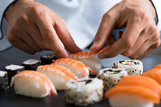 Primo piano delle mani di chef che preparano cibo giapponese Foto Premium