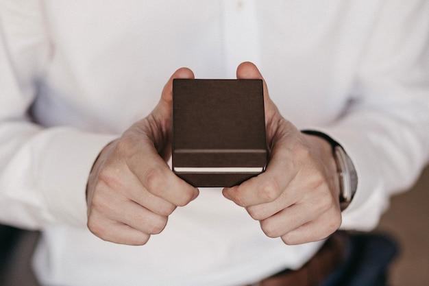Primo piano del regalo sulle mani maschii. uomo in camicia bianca. uomo irriconoscibile che tiene casella attuale marrone. giorno speciale e concetto di evento festivo. 2 mani dell'uomo con lo spazio della copia. Foto Premium