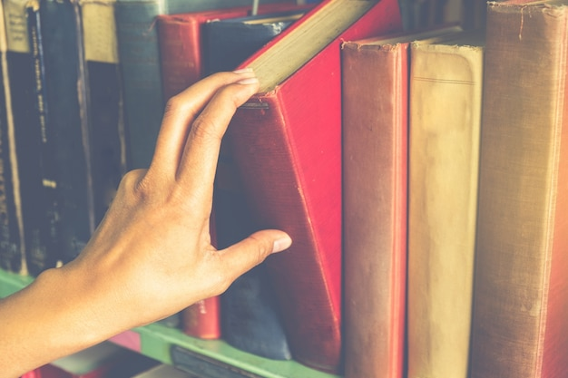 Closeup mano selezione libro da una libreria Foto Premium