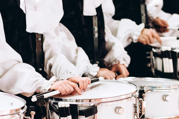 Un primo piano delle mani di un batterista in una parata. completo da bambino in camicie bianche. nuovo rullante bianco, bastoncini bianchi. il concetto di una parata e una marcia militari. Foto Premium