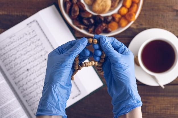 Primo piano le mani di preghiera in guanti medici blu con rosario di legno sullo sfondo del libro corano, tazza di tè, piatto di frutta secca, concetto iftar, mese di ramadan in quarantena, vista dall'alto Foto Premium