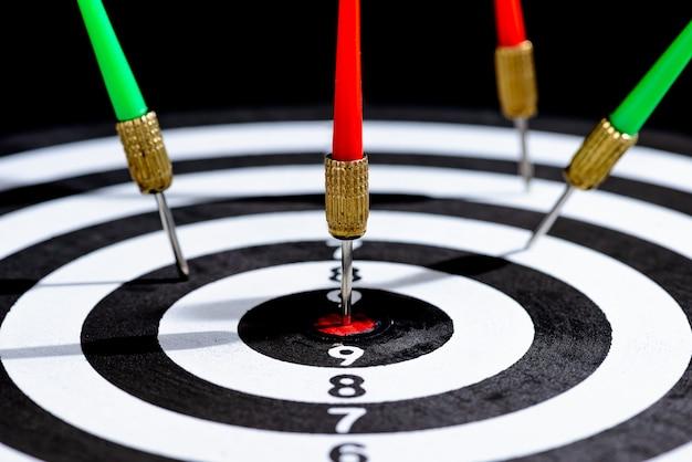 Primo piano testa di frecce dardo colpire centro bersaglio freccette sulla superficie nera Foto Premium