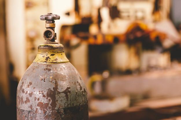 Vecchia valvola arrugginita del serbatoio di gas del primo piano, bombola a ossigeno di industria di non sicurezza del pericolo. Foto Premium