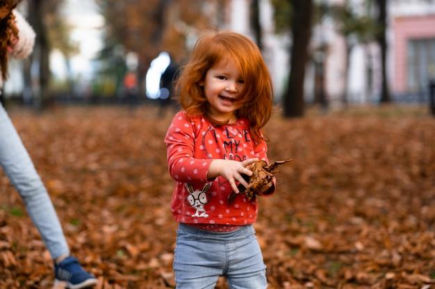 Closeup ritratto di carino adorabile sorridente poco dai capelli rossi caucasica ragazza bambino che gioca con le foglie secche in piedi in autunno caduta park fuori, guardando a porte chiuse, felice stile di vita concetto di infanzia Foto Premium