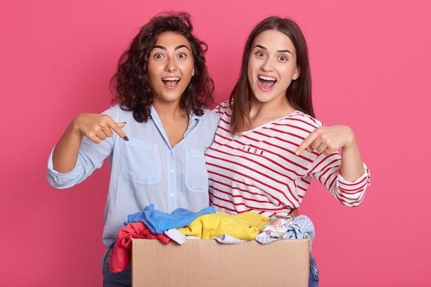 Un ritratto del primo piano di due ragazze emozionanti che indicano al contenitore di cartone con i vestiti per usando secondario Foto Premium