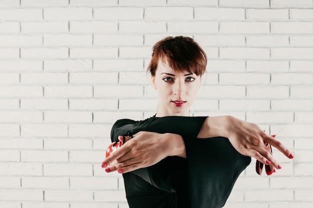 Vista del primo piano di una bella donna in abito nero, ballando con nacchere rosse Foto Premium