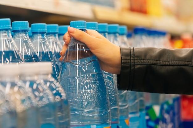 Le mani delle donne del primo piano tengono le drogherie nel deposito. il concetto di acquisto di frutta e verdura in un ipermercato durante la quarantena Foto Premium
