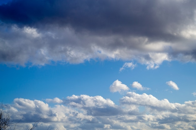 Nuvole sopra e sotto e cielo blu nel mezzo. primavera giornata di sole. bellissimo sfondo della natura. Foto Premium