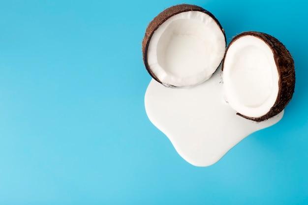 Crema di cocco o burro con noci di cocco fresche su sfondo blu. succo di panna bianca che gocciola dal cocco. Foto Premium