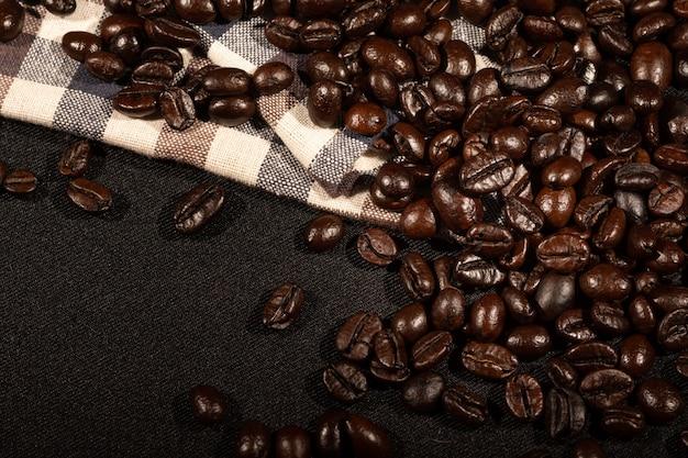 Chicchi di caffè sulla superficie marrone del tessuto di tela Foto Premium