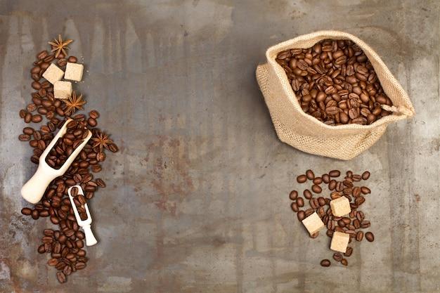 Chicchi di caffè in un sacco di iuta e su un tavolo di metallo arrugginito in una vista dall'alto Foto Premium