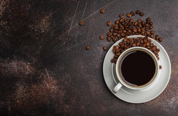 Chicchi di caffè e caffè in una tazza bianca su uno sfondo arrugginito scuro. vista dall'alto, copia dello spazio Foto Premium