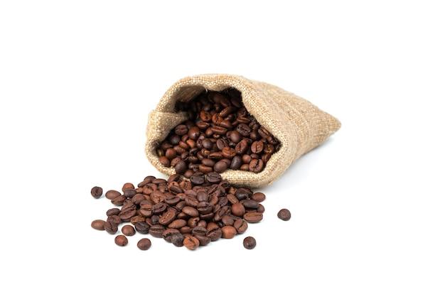 I chicchi di caffè da un sacchetto di tela vengono versati sul tavolo su uno sfondo bianco. Foto Premium
