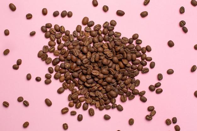 Chicchi di caffè sul rosa Foto Premium