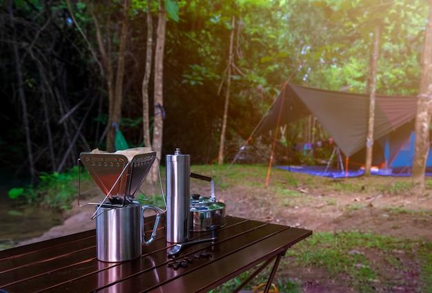 Gocciolamento del caffè mentre accampandosi nel parco naturale Foto Premium