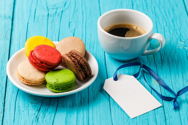 Caffè, amaretti e carta vuota sulla tavola di legno blu Foto Premium