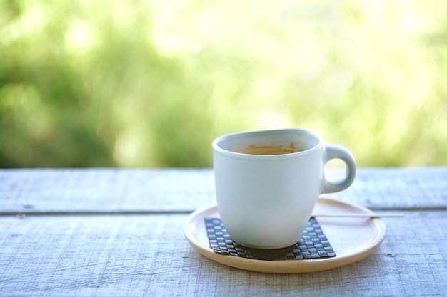 Caffè al mattino sul tavolo di legno con sfocatura backgroundxa della natura Foto Premium