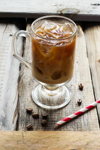 Caffè con ghiaccio in vetro e chicchi di caffè Foto Premium