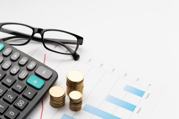 Pila di monete sopra il grafico con gli occhiali Foto Premium