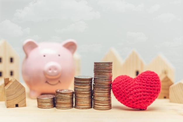 Pila della moneta con il modello e il porcellino salvadanaio domestici di legno per i soldi di risparmio per comprare una nuova casa con il concetto del cuore di amore. Foto Premium