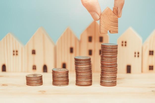 Pila della moneta con il modello domestico di legno per il risparmio dei soldi per comprare un nuovo concetto domestico. Foto Premium