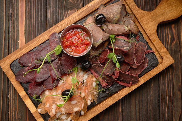 Salumi, salsiccia, basturma, carne affumicata, con salsa e olive, su una tavola di legno, su una tavola di legno Foto Premium