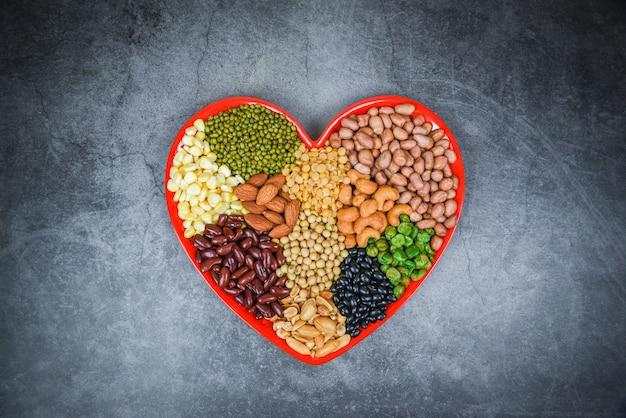 Collage vari fagioli mescolano piselli agricoltura di alimenti naturali sani per cucinare ingredienti - set di diversi cereali integrali fagioli e legumi semi lenticchie e noci colorate sulla composizione del cuore Foto Premium